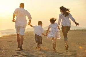 9717403 - happy young family have fun on beach run and jump at sunset